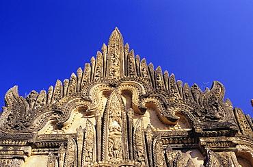Burma (Myanmar), Bagan, Tayyukpye Temple, detail of Stucco Reliefs on top, blue sky.