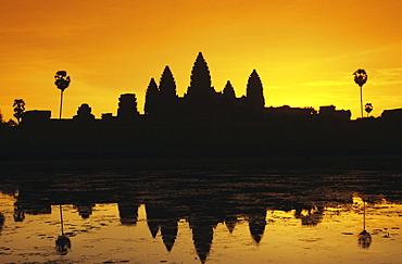 Cambodia, Siem Reap, Angkor Wat, silhouette of temple at sunrise, reflections on water surface, ornage sky