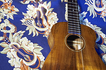 Detail of handmade koa ukulele on aloha print background