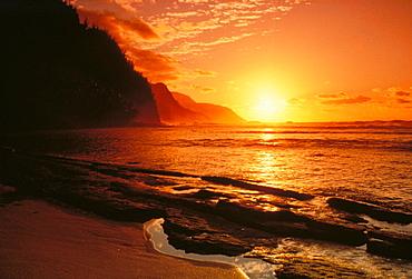 Hawaii, Kauai, NaPali Coast at sunset, bright orange sky and calm ocean.