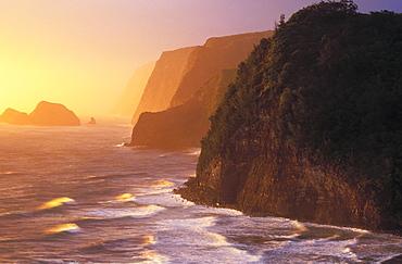 Hawaii, Big Island, North Kohala, Pololu coast and warm glowing surf sunrise,