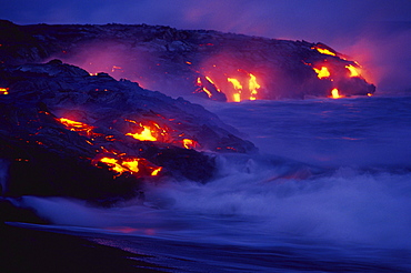Hawaii, Big Island, Hawaii Volcanoes National Park, Lava flows into ocean at night, creating a purple mist.