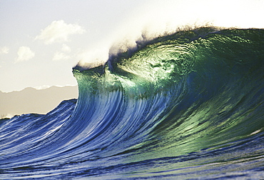 Hawaii, Oahu, North Shore; large green blue wave about to curl, mountains in background.