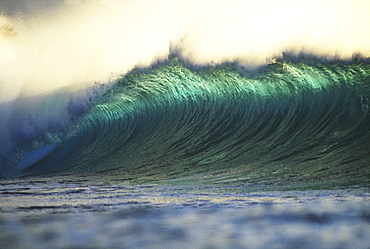 Hawaii, Oahu, North Shore, curling wave at world famous Pipeline at dusk.