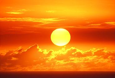 Hawaii, Oahu, Waikiki, View of huge orange sun sinking towards the horizon.