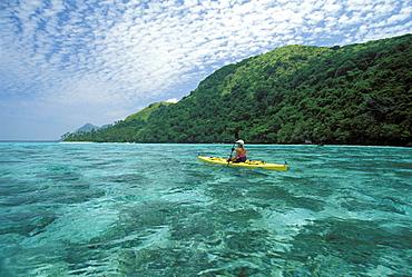 Fiji, Kadavu Islands, Woman kayaking in shallow water along coastline.
