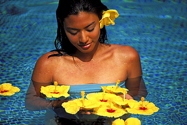 Young Polynesian woman in pool surrounded by floating yellow hibiscus looking down