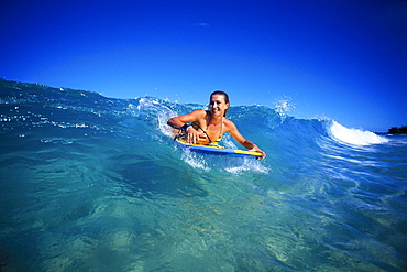 Hawaii, Woman body boarder Claudia Cox smiling as she catches wave