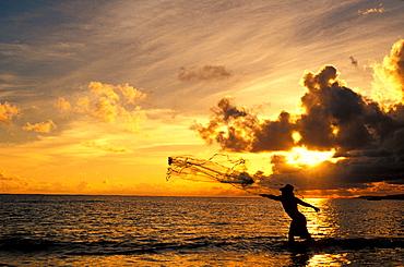 Fisherman throwing net at sunset