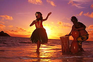 Hula dancer performing with drummer on beach at sunrise in background Hawaii