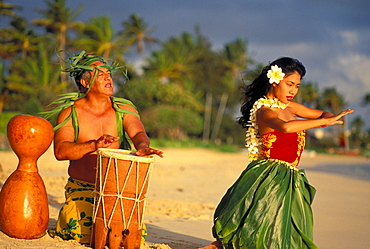 Hula dancer at sunrise on beach with Tahitian Drummer performing at water's edge