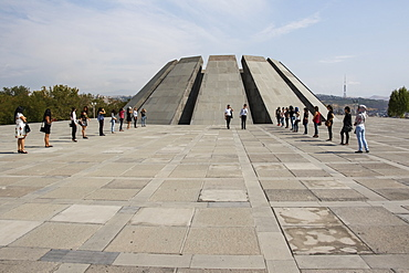 Young people in front of the twelve slabs positioned in a circle, representing the twelve lost provinces in present-day Turkey at the Armenian Genocide memorial complex on Tsitsernakaberd hill, Yerevan, Armenia