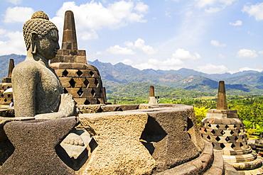 Buddha statue amidst the latticed stone stupas containing Buddha statues on the upper terrace, Borobudur Temple Compounds, Central Java, Indonesia