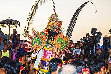 Garuda surrounded by men sitting in a circle chanting in trance during a Kecak dance performance, Ulu Watu, Bali, Indonesia