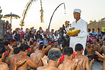 Priest carrying incense and water for blessings surrounded by men sitting in a circle chanting in trance during a Kecak dance performance, Ulu Watu, Bali, Indonesia