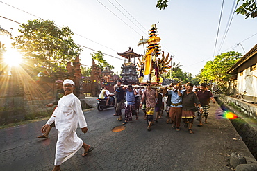 Balinese men carrying the wadah, a temple-shaped structure made of paper and light wood, containing the ashes of the deceased in a funeral procession to deposit the ashes in the Unda river following the Ngaben or Cremation Ceremony, Klungkung, Bali, Indonesia