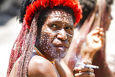 Dani woman smoking a cigarette, Obia Village, Baliem Valley, Central Highlands of Western New Guinea, Papua, Indonesia