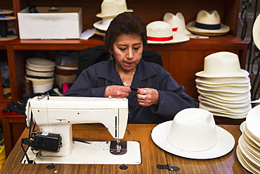 Woman sewing the black brim on to a panama hat at the Barranco Panama Hat Factory, Cuenca, Azuay, Ecuador