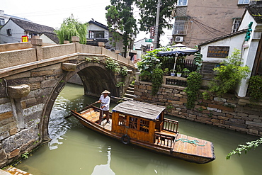 Man punting a boat by a bridge over the North-South canal by Pingjiang Road, Suzhou, Jiangsu, China