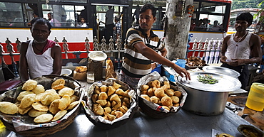 Indian men selling savoury snacks from a street food stall