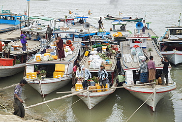Boats tied up on the Mandalay shore of the Irrawaddy River teaming with activity as they load goods and passengers, Mandalay, Myanmar