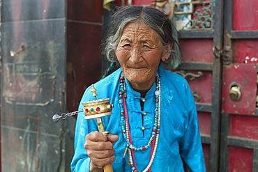 Elderly woman spins prayer wheel, Manigange, Sichuan, China