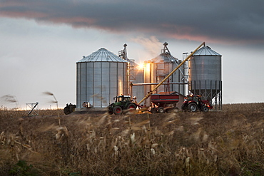 Grain silos and tractor under a dramatic sky at sunset, Quebec, Canada