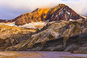 The eastern peak of Trident Volcano rises above the ash-covered Knife Creek Glaciers at sunset in Katmai National Park; Alaska, United States of America