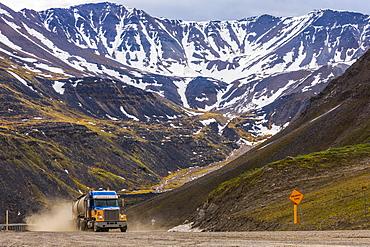 A semi-truck ascends through Atigun Pass along the Dalton Highway; Alaska, United States of America