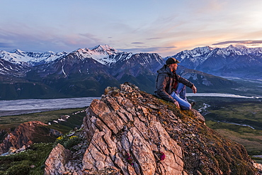 A man observes a tranquil sunset from an alpine perch in the Alaska Range high above the Delta River; Alaska, United States of America