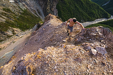 A man climbs a steep ridge above Whistler Creek in the eastern Alaska Range; Alaska, United States of America