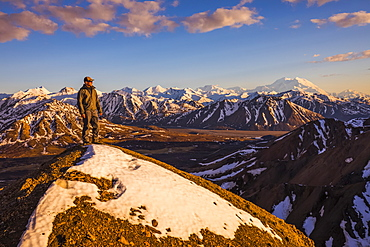 A man on a snowy ridge near Polychrome Mountain in Denali National Park faces the sunset with Denali in the background; Alaska, United States of America