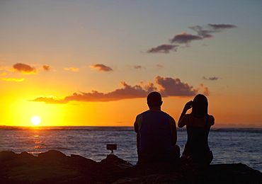 Silhouette of a couple taking pictures and watching the sunset on the beach, Waikiki; Honolulu, Oahu, Hawaii, United States of America