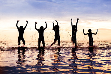 Silhouette of five children jumping out of the water in a row at sunset,Sandbanks Provincial Park; Picton, Ontario, Canada