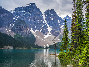 Moraine Lake and the rugged peaks of the Canadian Rocky Mountains with a boat in the water; Lake Louise, Alberta, Canada