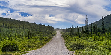 Two cyclists ride down a gravel road between hills and forest; Canada
