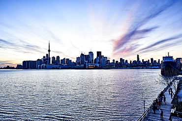 Tourists On A Boardwalk With A View Of The Downtown City Skyline At Dusk; Toronto, Ontario, Canada