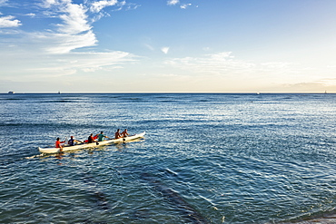 Tourists paddle in an outrigger canoe off Waikiki Beach, Waikiki, Oahu, Hawaii, United States of America