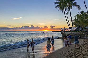 Tourists watch and photograph sunset on Waikiki Beach, Honolulu, Oahu, Hawaii, United States of America