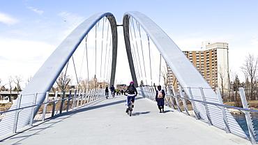 Pedestrians and cyclists going across a bridge over the Bow River, Calgary, Alberta, Canada