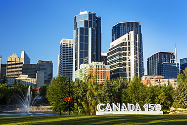 Canada 150 signage in city park with Calgary building towers in background with blue sky, Calgary, Alberta, Canada