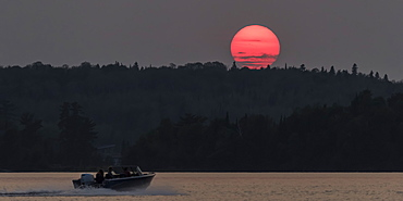 A bright pink sun sinking below a silhouetted hill and forest and a motorboat splashes on a lake, Kenora, Ontario, Canada