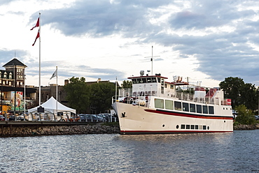 A tour boat moored along the shoreline of Lake of the Woods at sunset, Kenora, Ontario, Canada