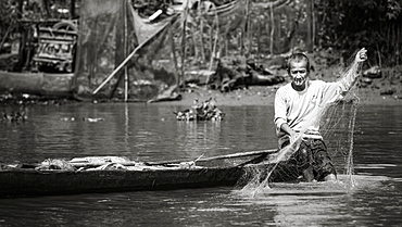 A man smoking a cigarette while fishing from his boat on the Mekong River, Mekong Delta, Thoi An, Can Tho, Vietnam