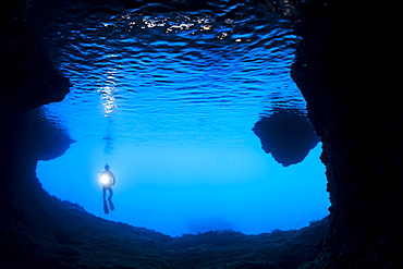 Diver at the entrance to a cavern off the island of Gato, Bohol Sea, Philippines
