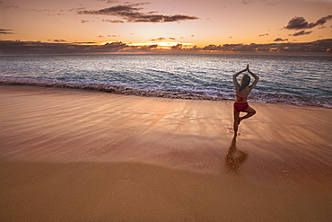 Woman in a yoga pose on the beach at sunset, Molokai, Oahu, Hawaii, United States of America