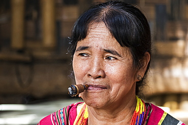 Lavae woman smoking a cigar in the ethnic village at Pha Suam, Bolaven Plateau, Champasak, Laos