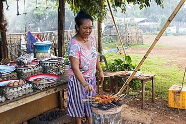 Woman barbecuing satay, Pha Suam, Bolaven Plateau, Champasak, Laos