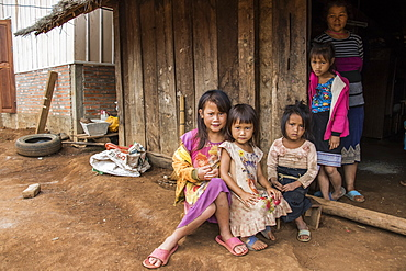 Hmong woman and four girls in front of their house in Na Kam Peng, also called Bomb Village, Xiangkhouang, Laos
