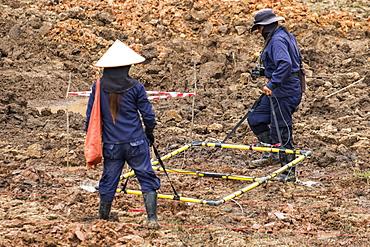 Women using a metal detector while clearing landmines in a field near Phonsavan, Xiangkhouang, Laos